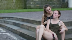 Two cute teen girls girlfriends talking sitting together on the stone steps in the Park. Two teen girls girlfriends talking sitting together on the stone steps stock video