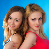 Two cute teenage girls on blue background Royalty Free Stock Photo