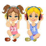 Two cute teenager girls sitting together on floor listening music with headphones Stock Photo