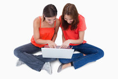 Two cute teenagers sitting cross-legged. While looking at a laptop against a white background Royalty Free Stock Photography