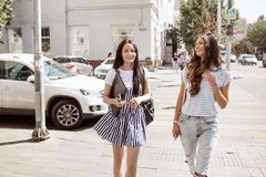 Two cute thin girls with long hair,wearing casual outfit, are walking down the street on a sunny day. stock image