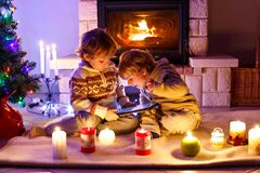 Two cute toddler boys, blond twins playing with new tablet gift. Family celebrating Christmas holiday Stock Photos