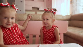 Two cute twin sisters are dressed in red polka-dot dresses. They play together, hug, smile at each other. Two cute twin sisters are dressed in red polka-dot stock video