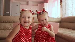 Two cute twin sisters are dressed in red polka-dot dresses. Playing together kiss each other smiling. Two cute twin sisters are dressed in red polka-dot dresses stock video