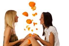 Two cute twins girls having fun under orange rain. On a white background Stock Photography