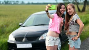 Two cute women making selfies on roadtrip. Two cute women stopped car on a roadside of rural road during trip. Young smiling women making selfies on the phone stock video