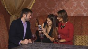 Two cute women and a man sitting in a restaurant and use the phone. Two cute women and a man sitting in a restaurant and looking at the pictures in the stock video footage