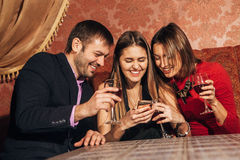 Two cute women and a man sitting in restaurant use the phone. Two cute women and a men sitting in a restaurant and looking at the pictures in the smartphone and Stock Photo