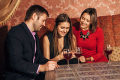Two cute women and a man sitting in restaurant use the phone. Two cute women and a men sitting in a restaurant and looking at the pictures in the smartphone and Royalty Free Stock Image