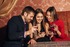 Two cute women and a man sitting in restaurant use the phone. Two cute women and a men sitting in a restaurant and looking at the pictures in the smartphone and Stock Photography