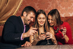 Two cute women and a man sitting in restaurant use the phone. Two cute women and a men sitting in a restaurant and looking at the pictures in the smartphone and Royalty Free Stock Photos