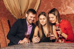 Two cute women and a man sitting in restaurant use the phone. Two cute women and a men sitting in a restaurant and looking at the pictures in the smartphone and Stock Photos
