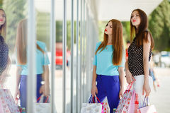 Two cute women view showcases the supermarket. Stock Photography