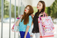 Two cute women view showcases the supermarket. Royalty Free Stock Image