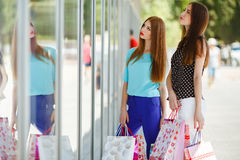 Two cute women view showcases the supermarket. Royalty Free Stock Images