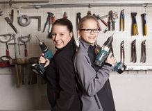 Two Cute Worker Woman. With battery screwdriver royalty free stock images