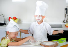 Two cute young children learning to bake Royalty Free Stock Image