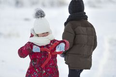 Two cute young children in warm clothing with bright snow clips stock photos