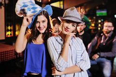 Cute young girlfriends in Bavarian hats smiling at the bar background during the celebration of the Oktoberfest stock photo