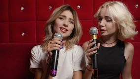 Cute young girlfriends sing karaoke on a red quilted background