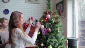 Two cute young girls decorating the Christmas tree. Beautiful brunette decorating the tip of the Christmas tree with multicolored balls and toys. Pretty blonde stock video footage