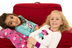 Two cute young girls relaxing in winter pajamas Royalty Free Stock Images