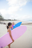 Two cute young girls walking together with surfboards at beach Stock Photos