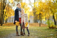 Two cute young sisters having fun on beautiful autumn day. Happy children playing in autumn park. Kids gathering yellow fall royalty free stock photo