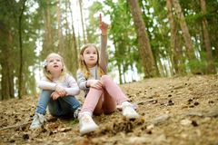 Two cute young sisters having fun during forest hike on beautiful early spring day. Active family leisure with kids. Family fun stock images