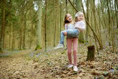 Two cute young sisters having fun during forest hike on beautiful early spring day. Active family leisure with kids. Family fun stock photography