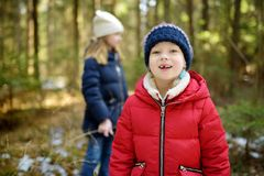 Two cute young sisters having fun during forest hike on beautiful winter day. Active family leisure with kids. Family fun stock photo