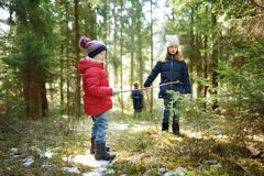 Two cute young sisters having fun during forest hike on beautiful winter day. Active family leisure with kids. Family fun stock photography