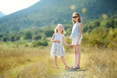 Two cute young sisters laughing and hugging on warm and sunny summer day during family vacations in Greece royalty free stock image