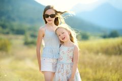 Two cute young sisters laughing and hugging on warm and sunny summer day during family vacations in Greece stock photography