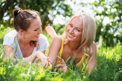Two cute young women lying in the grass on summer sunny day outd Stock Images