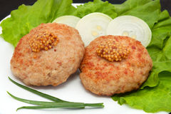 Two cutlets with mustard. Grilled cutlets on the leaves of lettuce and onion on a plate, isolation on a white background Stock Images