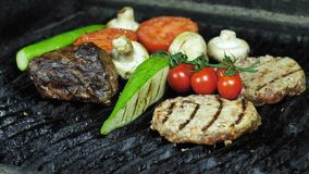 Two cutlets, a piece of beef and vegetables grilled zucchini cherry tomatoes and mushrooms are grilled royalty free stock photo