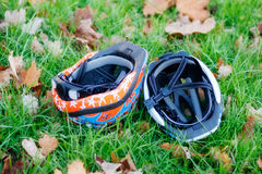 Two cycling helmets upside-down in the grass. Two cycling helmets in the grass. Outdoor cycling in park with kids. A weekend in November stock image