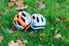 Two cycling helmets upside-down in the grass Royalty Free Stock Photos