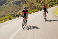 Two cyclist practicing for triathlon race. Triathletes practicing cycling on country road. Man and women riding bicycle on open road stock image
