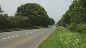 Two cyclist riding down a country road stock video