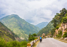 Two cyclist riding on hi-mountain road. Manali-Leh road in Indian Himalayas, Jammu and Kashmir State, North India Royalty Free Stock Image