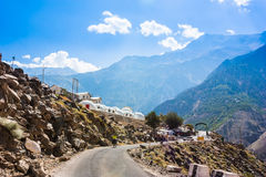 Two cyclist riding near high mountain village in Himalayas Stock Photo