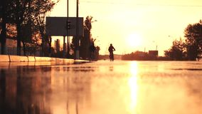Two cyclist riding at sunset in the rain stock video footage