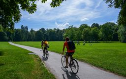Two cyclists on a asphalt cycling lane in the English garden, a famous park in the centre of Munich, Germany stock photography