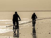 Two Cyclists on the beach Stock Image