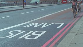 Two cyclists on Boris Bikes. Cross London Bridge in a bus lane. Footage is 4K stock footage