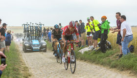 Two Cyclists on a Cobblestone Road - Tour de France 2015 Stock Photos