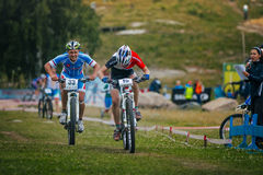 Two cyclists competing at the finish. Sludorudnik, Russia - August 06, 2015:  two cyclists competing at the finish during Spartakiada among boys and girls in Royalty Free Stock Photo