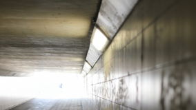Two Cyclists Cycling through a Tunnel Into the Light of Day. Static medium long high angle shallow depth of field shot of two cyclist cycling through a tunnel stock video footage